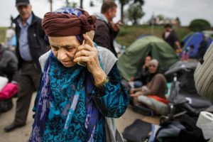 SID, SERBIA - SEPTEMBER 22: A migrant speaks on a smartphone as she and other migrants wait in a holding area just metres across from the Croatian border after walking the last few kilometres from Serbia to Croatia on September 22, 2015 in Sid, Serbia. Thousands of migrants have arrived in Austria over the weekend with more en-route from Hungary, Croatia and Slovenia. Politicians across the European Union are to hold meetings on the refugee crisis with EU interior ministers meeting tomorrow and EU leaders attending an extraordinary summit on September 23. (Photo by Carsten Koall/Getty Images)
